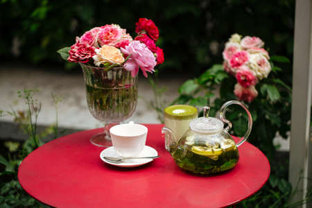 Morning summer tea set in the garden on a red table decorated with flowers Фото со стока