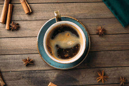 Top view of freshly brewed aromatic black coffee on the dark wooden background decorated with spices Фото со стока - 156429619