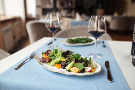 Fresh vegetables salad on the served restaurant table with glasses of red wine Фото со стока - 156429822