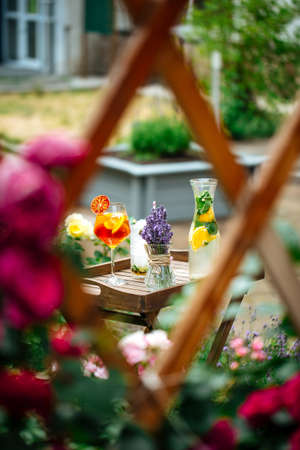 View through fence on a variety of cold lemonade and cocktails on the wooden tray decorated with lavander Фото со стока