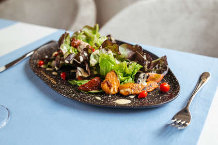 Gourmet chicken salad with greens and white sauce on the served restaurant table Фото со стока