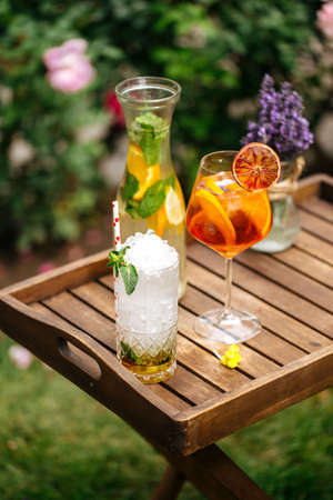 Variety of cold lemonade and cocktails on the wooden tray decorated with lavander Фото со стока - 156429673