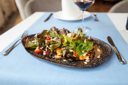 Gourmet chicken salad with greens and white sauce on the served restaurant table Фото со стока - 156429665