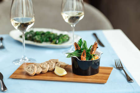 Spanish dish gambas pil-pil shrimps with toasts and white wine on the restaurant table