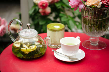 Morning summer tea set in the garden on a red table decorated with flowers Фото со стока - 156429624