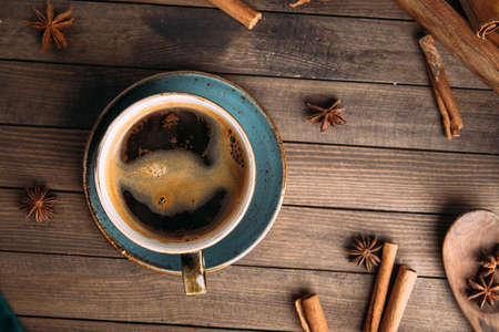 Top view of freshly brewed aromatic black coffee on the dark wooden background decorated with spices Фото со стока