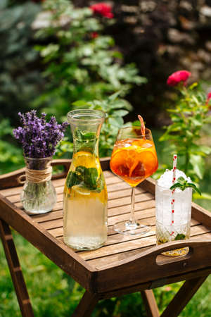 Variety of cold lemonade and cocktails on the wooden tray decorated with lavander