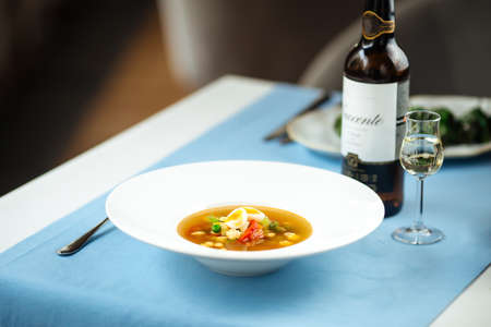 Gourmet vegetable soup on the served table with a bottle of wine Фото со стока - 156429846