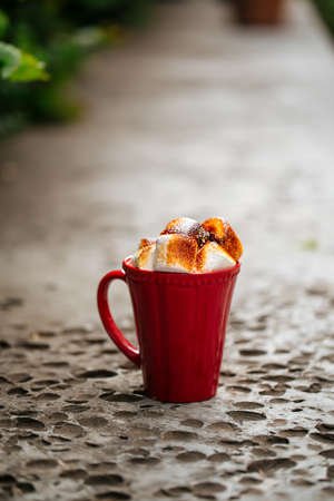 Hot beverage with toasted marshmallows in red mug on stone background Фото со стока - 156429583