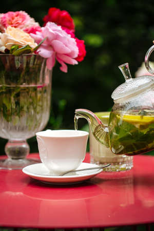 Pouring green tea in a white cup on the red table decorated with roses in a vase