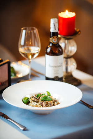 Gourmet tagliatelle with wild mushrooms in a white plate on the served restaurant table Фото со стока - 156429646