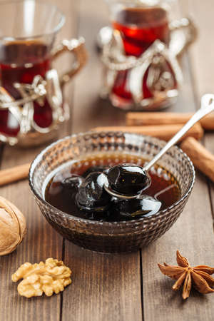 Dark walnut jam in a glass bowl on wooden decorated background Фото со стока - 156506517