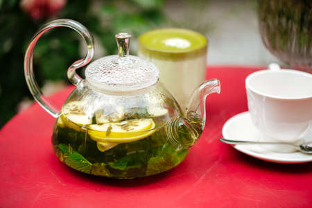 Closeup on glass teapot with mint green tea and cup on the red table Фото со стока - 156512078