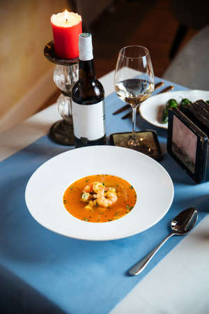 Gourmet spanish seafood soup on the served table with a bottle of wine Фото со стока