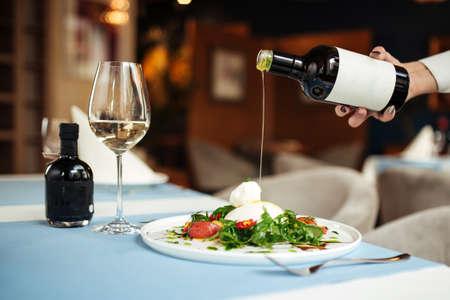 Pouring oil on spanish buratta salad on the restaurant table Фото со стока - 156506742