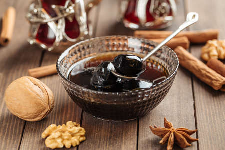 Dark walnut jam in a glass bowl on wooden decorated background