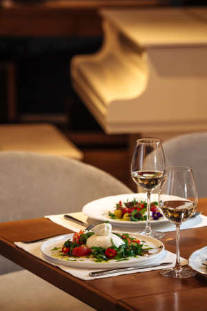 Restaurant table served with spanish buratta tomato salads Фото со стока - 156506513