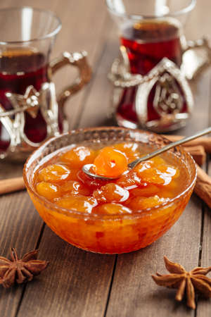 White cherry jam in a glass bowl on wooden decorated background