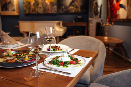 Restaurant table served with spanish buratta tomato and peppers salads and paella Фото со стока - 156506734