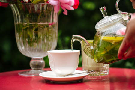 Pouring green mint tea from glass teapot in white cup on the red table Фото со стока - 156511958