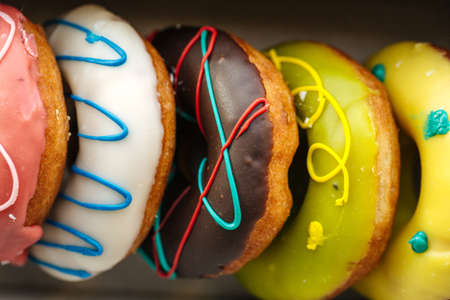 Closeup on assortment of colorful donuts with different toppings Фото со стока - 156511944