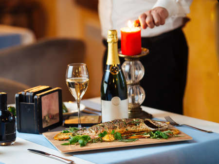 Restaurant table with grilled sea bass with waiter lighting a candle on the background