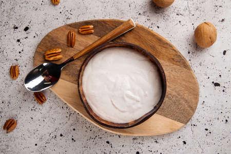 Top view on healthy breakfast yogurt in wooden bowl on the light background Фото со стока - 156506886