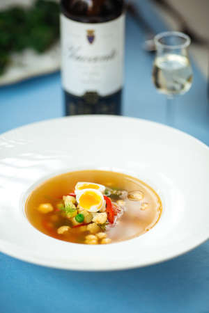 Gourmet vegetable soup on the served table with a bottle of wine