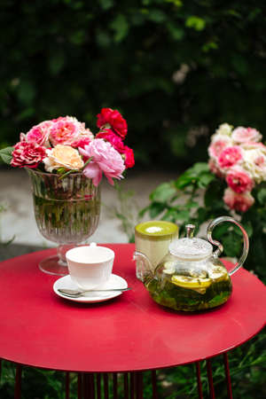 Morning summer tea set in the garden on a red table decorated with flowers Фото со стока - 156506449