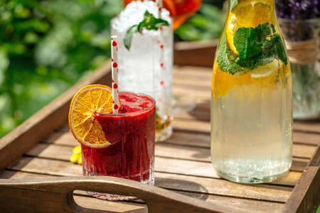 Closeup on variety of cold lemonade and cocktails on the wooden tray Фото со стока - 156506705