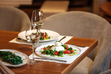 Restaurant table served with spanish buratta tomato and peppers salads Фото со стока - 156511917