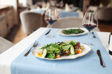 Fresh vegetables salad on the served restaurant table with glasses of red wine Фото со стока - 156512116