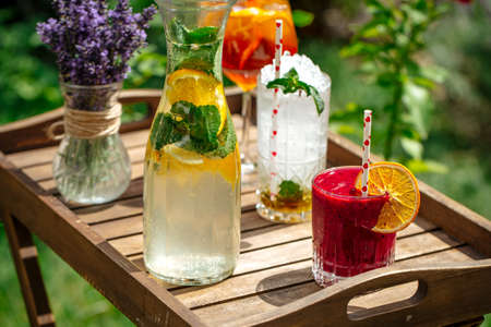 Closeup on variety of cold lemonade and cocktails on the wooden tray decorated with lavander Фото со стока - 156676839