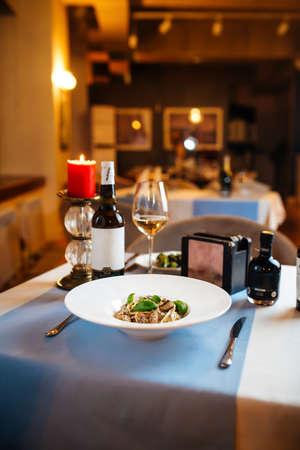Restaurant table served with tagliatelle with wild mushrooms in a white plate Фото со стока - 156512325