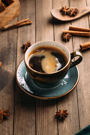 Freshly brewed aromatic black coffee on the dark wooden background decorated with spices Фото со стока
