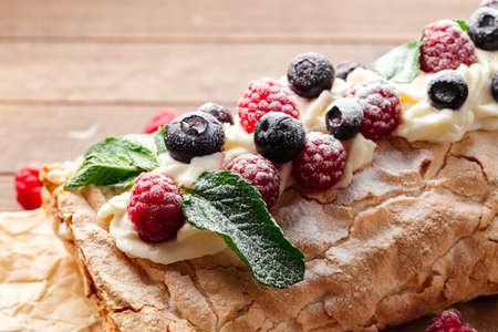 Closeup on meringue roll with berries sprinkled with powdered sugar