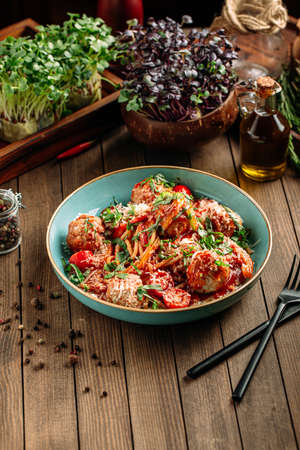 Spaghetti with meatballs under the grated cheese and sauce on the wooden background
