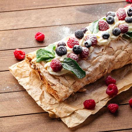 Closeup on meringue roll with berries sprinkled with powdered sugar Фото со стока - 157249720