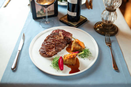 Side view on cut grilled beef ribeye steak with potatoes on white plate