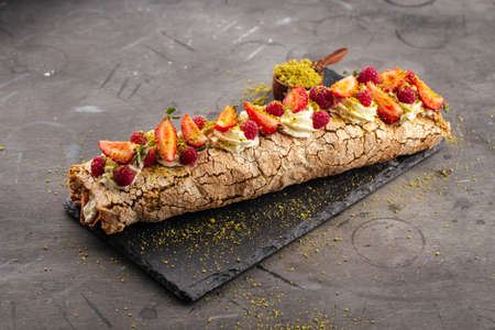 Side view on pistachio meringue roll with berries on the grey background