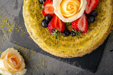 Top closeup on pistachio cheesecake garnished with berries and rose on gray concrete background Фото со стока