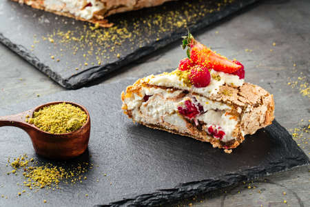 Side view on cut piece of pistachio meringue roll with berries on the grey background Фото со стока - 157560795