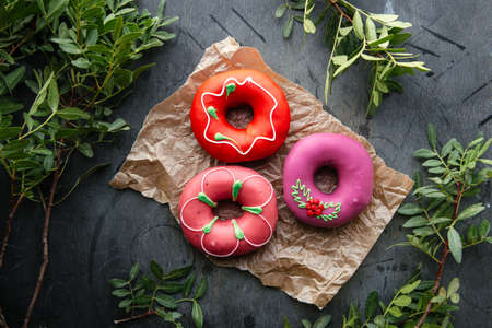Top view on different glazed donuts on a paper and dark background