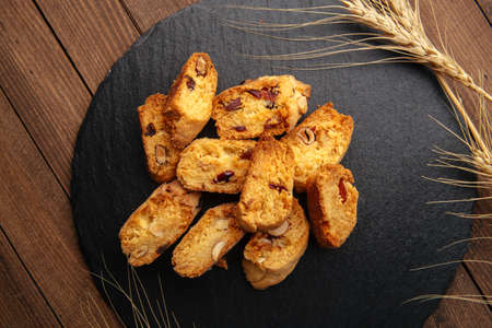 Top view on italian almond biscuits cantucci with dried cranberries on the black plate