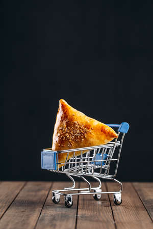 Oriental dish baked pie with meat triangle samsa in miniature trolley