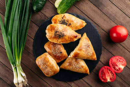 Top view on different oriental baked pie with meat samsa on the black stone plate Фото со стока
