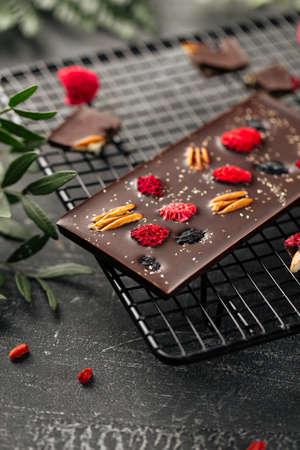 Closeup on handmade chocolate bar with pecan nuts and dried berries Фото со стока