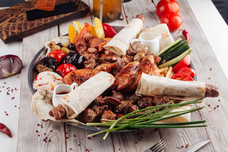 Side view on assorted caucasian grilled meat shashlyq platter on the light wooden table