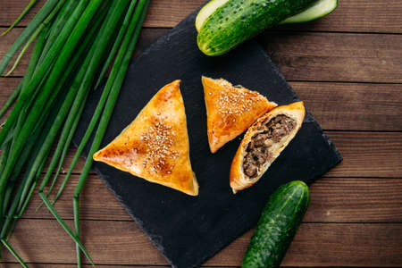 Top view cut oriental dish baked pie with meat triangle samsa on the black stone plate