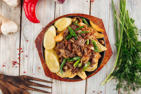 Top view on fried potatoes with beef and green onions in cast iron pan on the light wooden table Фото со стока